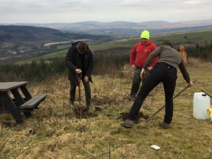 Image of three people around two holes being dug for the posts of a new picnic bench atop a mountain.