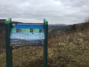 A picture of an information panel atop a mountain with the background valley stretched across the landscape