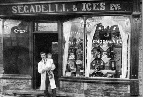 black and white photograph of a man holding his daughter on his hip outside Segadelli's sweet shop, Crynant.